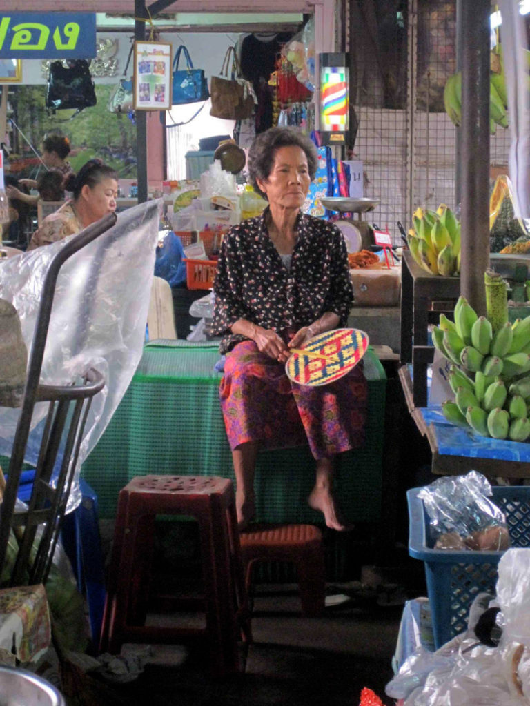 thai grandma at a market in bangkok